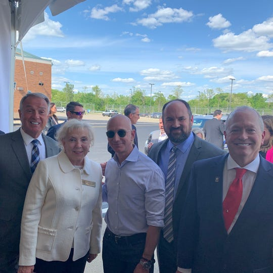 Boone County elected government leaders share a moment with Amazon CEO and founder Jeff Bezos, center, after Bezos broke ground May 14, 2019, using a front loader on a $1.5 billion Prime Air cargo hub at Cincinnati/Northern Kentucky International Airport. From left are Boone County Judge-executive Gary Moore, and Commissioner Cathy Flag, then Bezos, and Commissioners Jesse Brewer and Charlie Kenner.