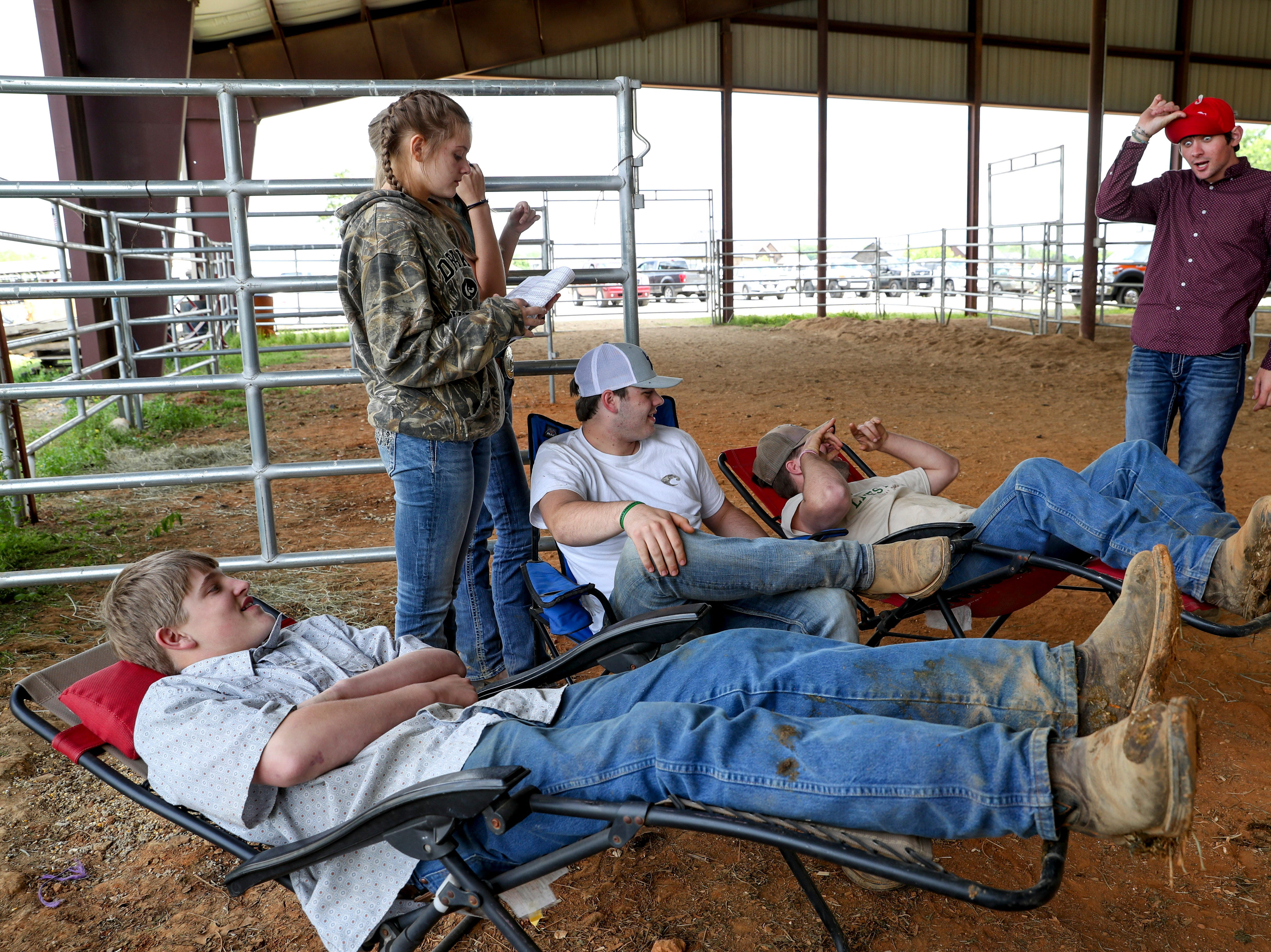 Friends lean back and joke around while the auction is going on at the 69th annual Clarksville Area Junior Better Beef Show at the John Bartee Agricultural Center in Clarksville, Tenn., on Tuesday, May 14, 2019.