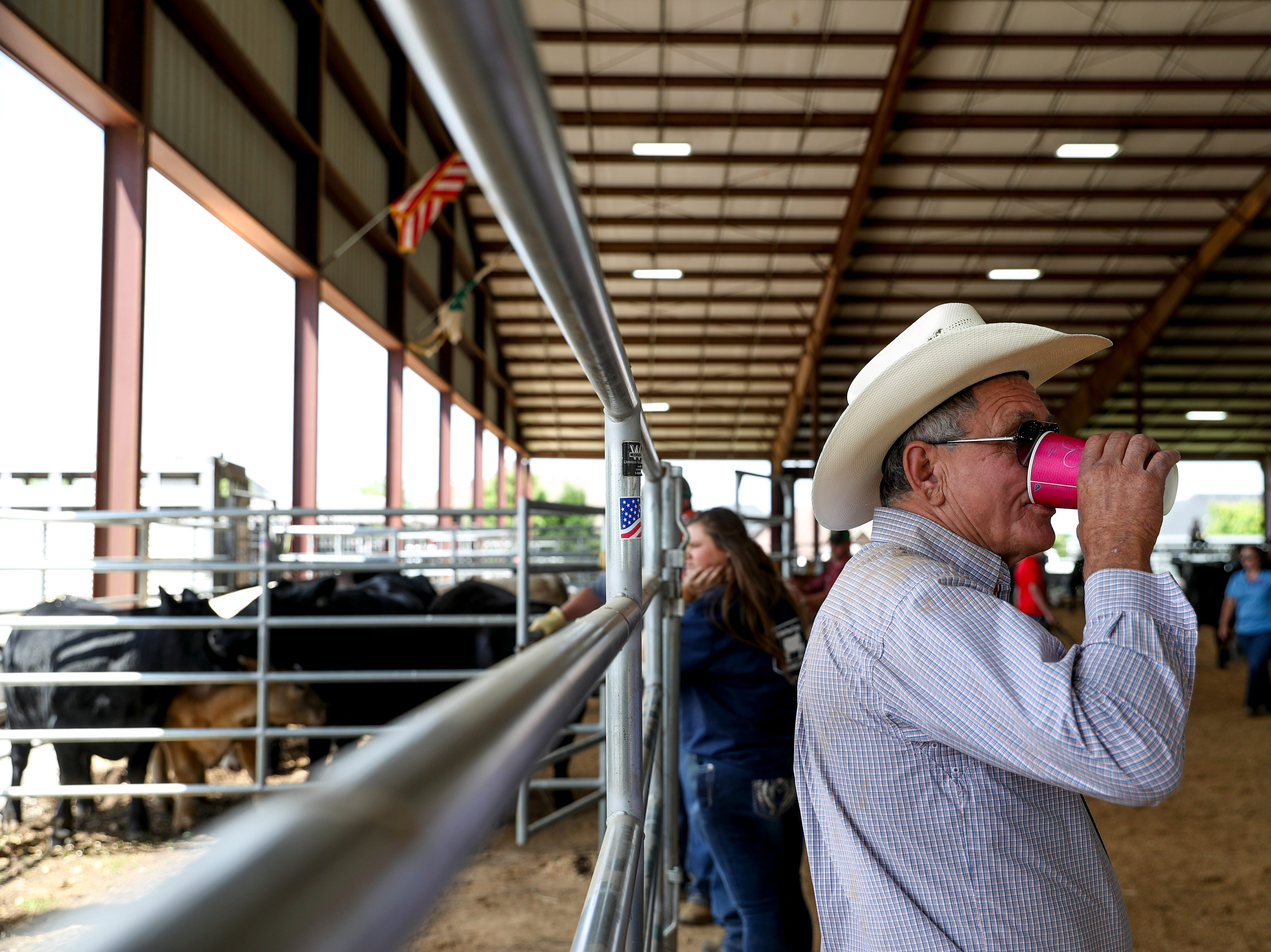Farmers stand at the gates to holding pens for their truck trailers at the 69th annual Clarksville Area Junior Better Beef Show at the John Bartee Agricultural Center in Clarksville, Tenn., on Tuesday, May 14, 2019.