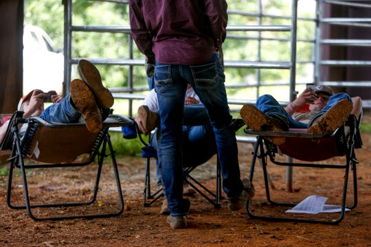 Kids hang out with their boots propped up and searching on their phones during the auction at the 69th annual Clarksville Area Junior Better Beef Show at the John Bartee Agricultural Center in Clarksville, Tenn., on Tuesday, May 14, 2019.