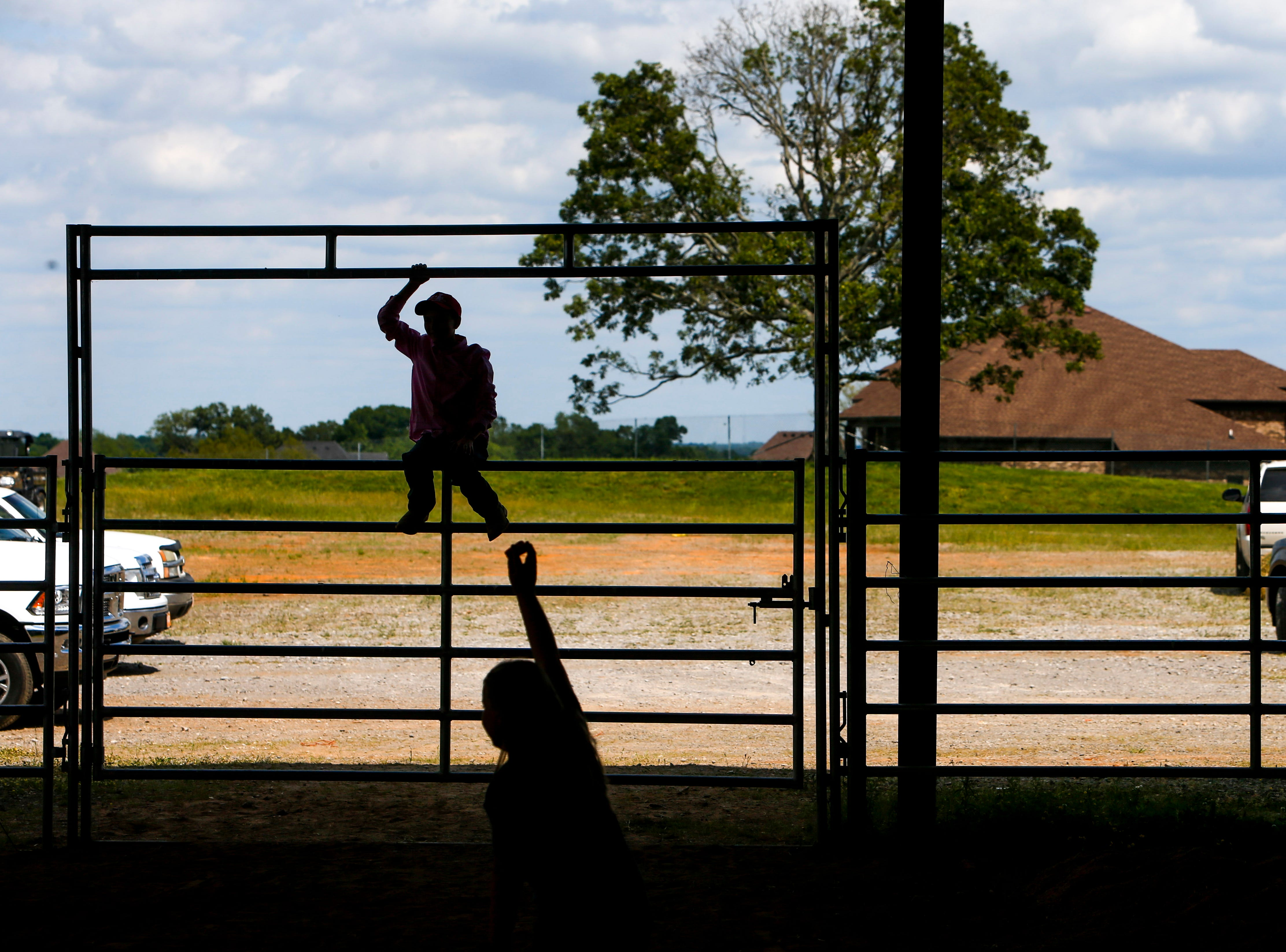 Kids play around and climb the fencing of the large event barn at the 69th annual Clarksville Area Junior Better Beef Show at the John Bartee Agricultural Center in Clarksville, Tenn., on Tuesday, May 14, 2019.