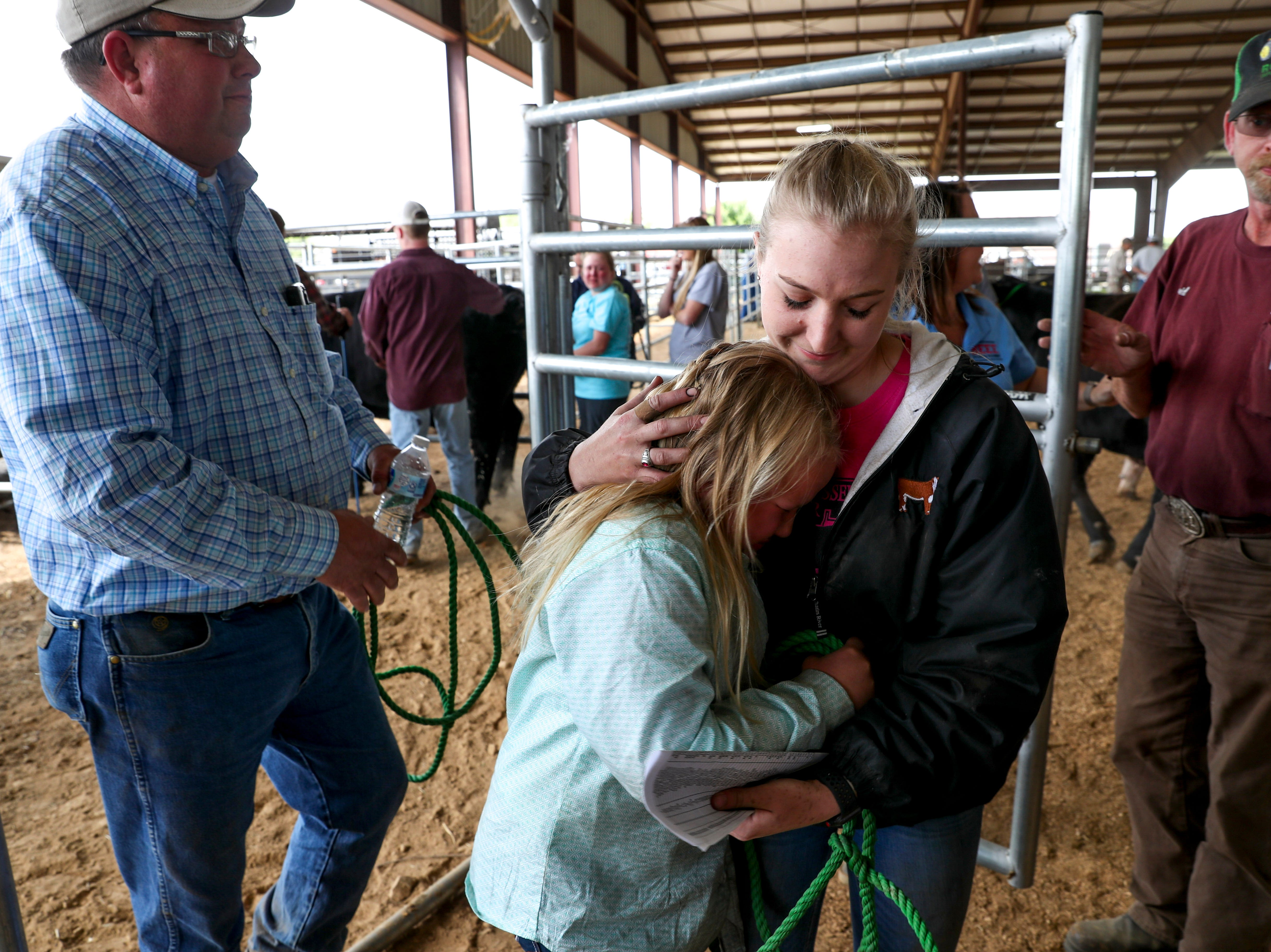 Cheyenne Coleman embraces her younger sister Ella Coleman, 10, that just said goodbye to her steer Cole at the 69th annual Clarksville Area Junior Better Beef Show at the John Bartee Agricultural Center in Clarksville, Tenn., on Tuesday, May 14, 2019.