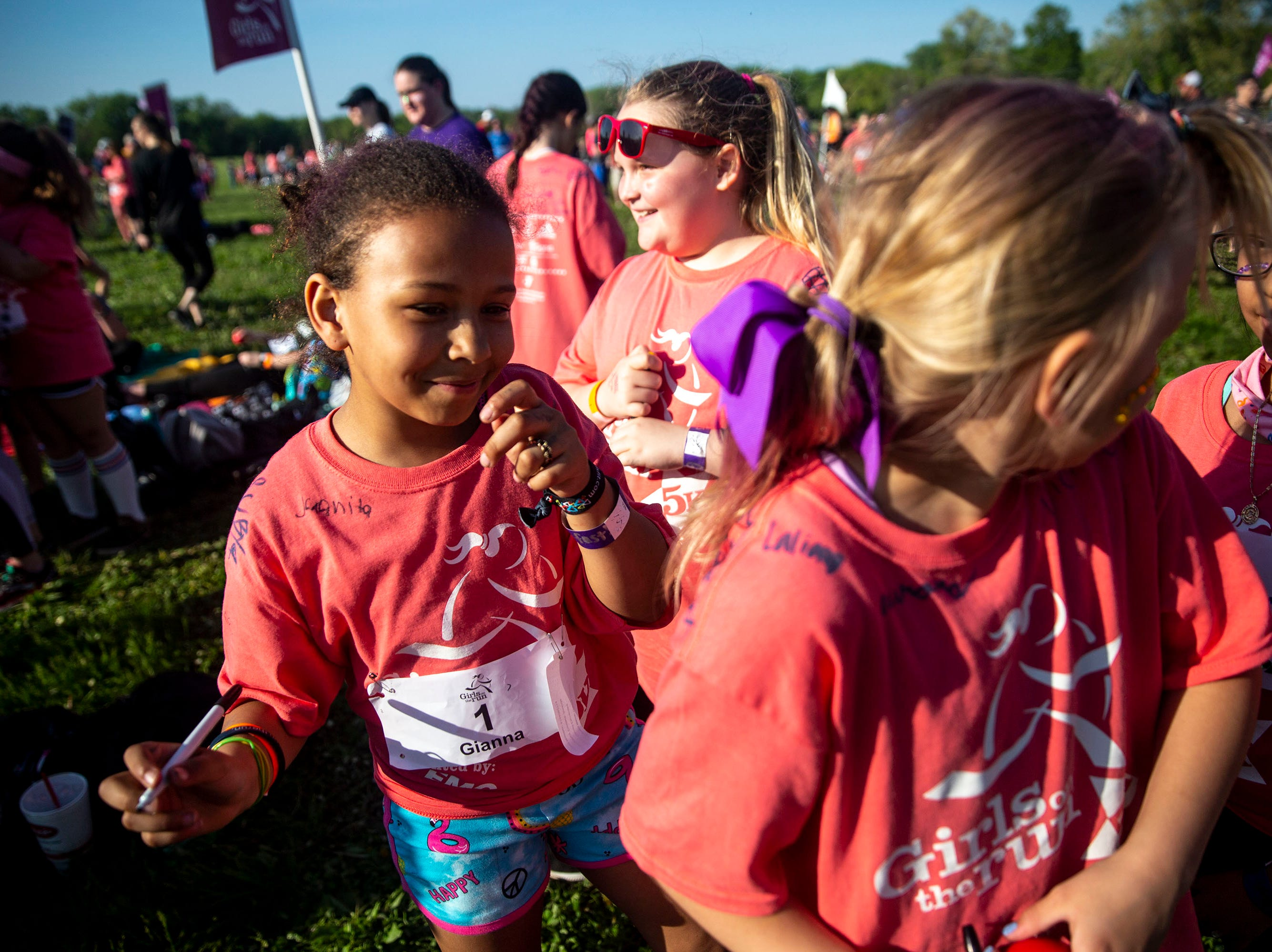Gianna Graham, of Des Moines, autographs Ruby Thompson's, of Des Moines, shirt before the Girls on the Run celebration 5K on Tuesday, May 14, 2019, in Water Works Park in Des Moines.