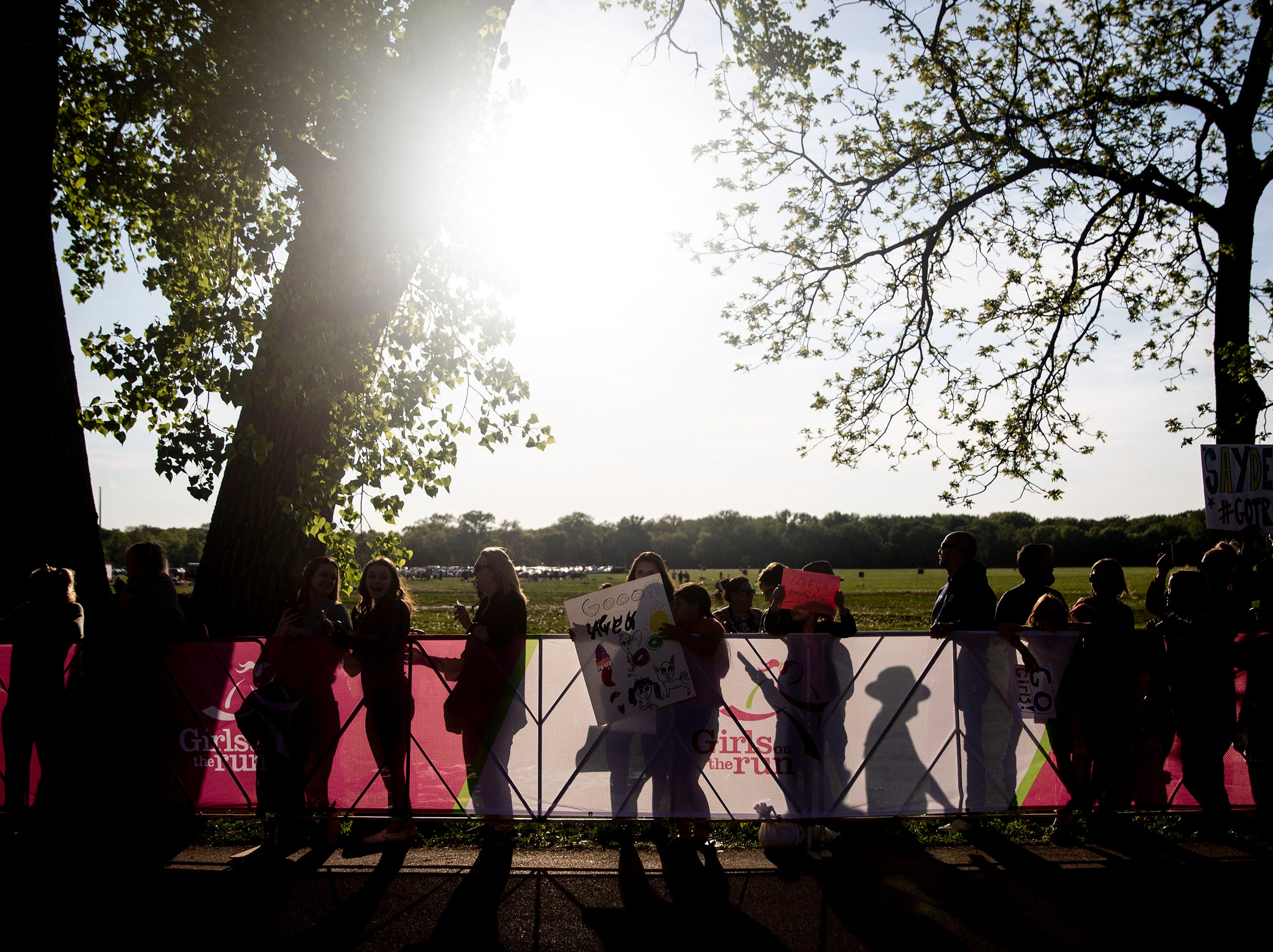 Spectators wait for runners to pass during the Girls on the Run celebration 5K on Tuesday, May 14, 2019, in Water Works Park in Des Moines.