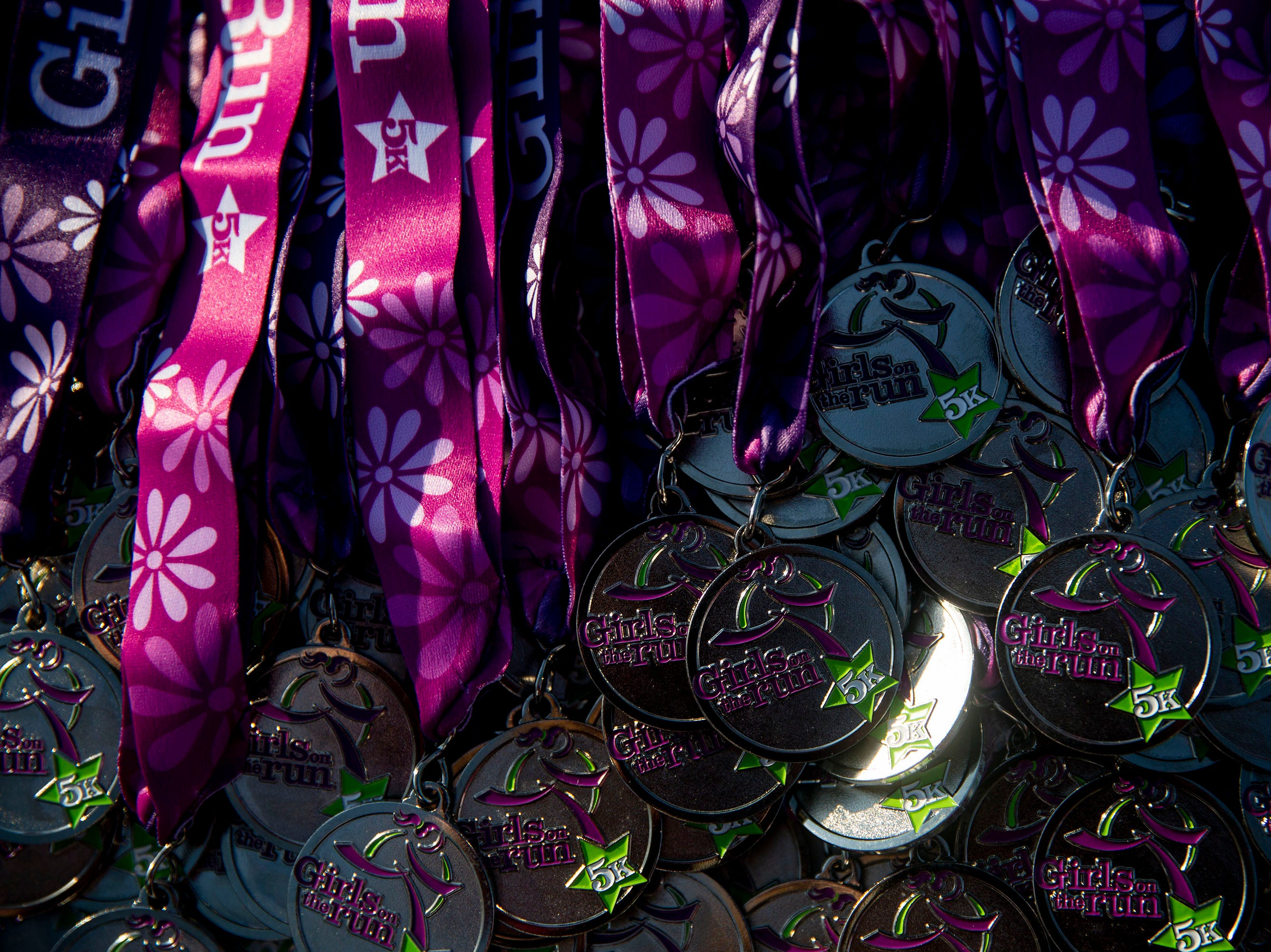 Medals wait for runners to finish the Girls on the Run celebration 5K on Tuesday, May 14, 2019, in Water Works Park in Des Moines.