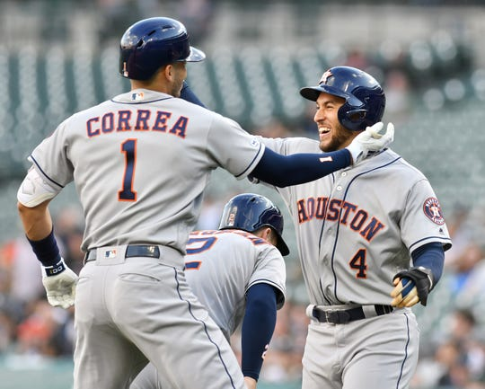 Astros' Aldemys Diaz celebrates with Carlos Correa after Correa's three-run home run in the first inning.