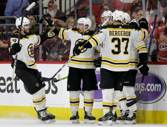 Boston Bruins' Jake DeBrusk, left, celebrates with Brad Marchand, Patrice Bergeron (37) and teammates following Marchand's goal against the Carolina Hurricanes during the second period in Game 3 Tuesday. Boston won 2-1 to take a 3-0 lead in the best-of-seven Eastern Conference finals series.