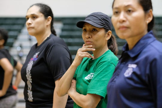 UOG women's basketball coach Cecile Olandez (center) looks on tryouts, with UOG Athletic Hall of Famer Susan Rechebong Lupola to her right.