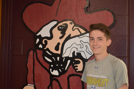 Samuel Cloutier poses in front of The Colonel at Henderson County High School.