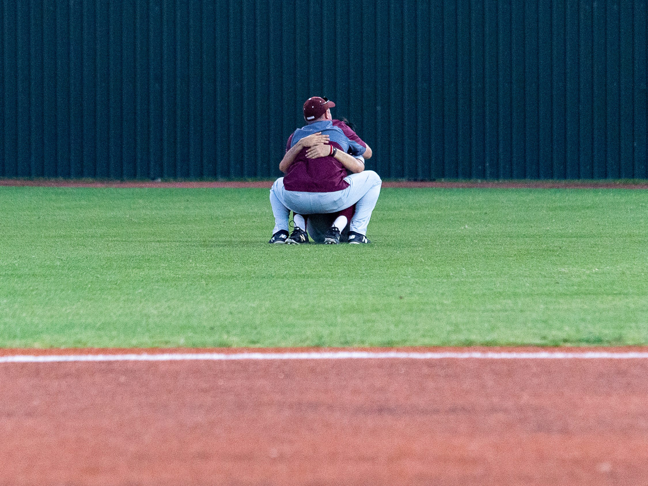 Herad Coach Kyle Cormier consoles a player as Breaux Bridge falls to Tioga High School in the LHSAA Class 4A Championship Game. Tuesday, May 14, 2019.