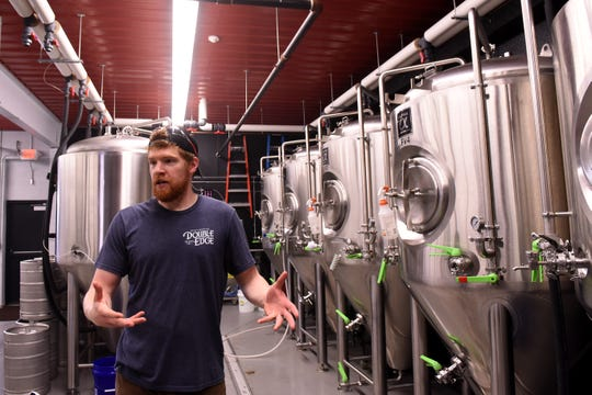 Zac Williams, co-owner of Double Edge Brewing Company, explains the beer brewing process in the brewing area attached to the businesses tap room.