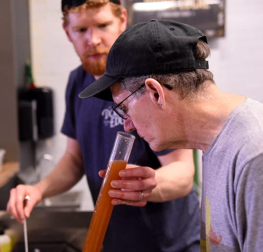 Zac Williams, co-owner of Double Edge Brewing Company, offers Eagle-Gazette reporter Jeff Barron a sniff of the in process Tangerine Wheat Beer being made that day.