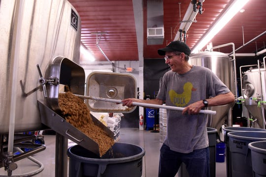 Eagle-Gazette reporter Jeff Barron shovels spent grain from the brewing process in to containers. The grain, which has steeped in hot water to form wort, is sent to be used as animal feed for livestock.