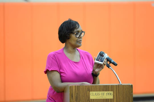 Corey Chatman's mother holds her phone up to the mic so that her son could speak remotely to the Mansfield School Board on Tuesday.