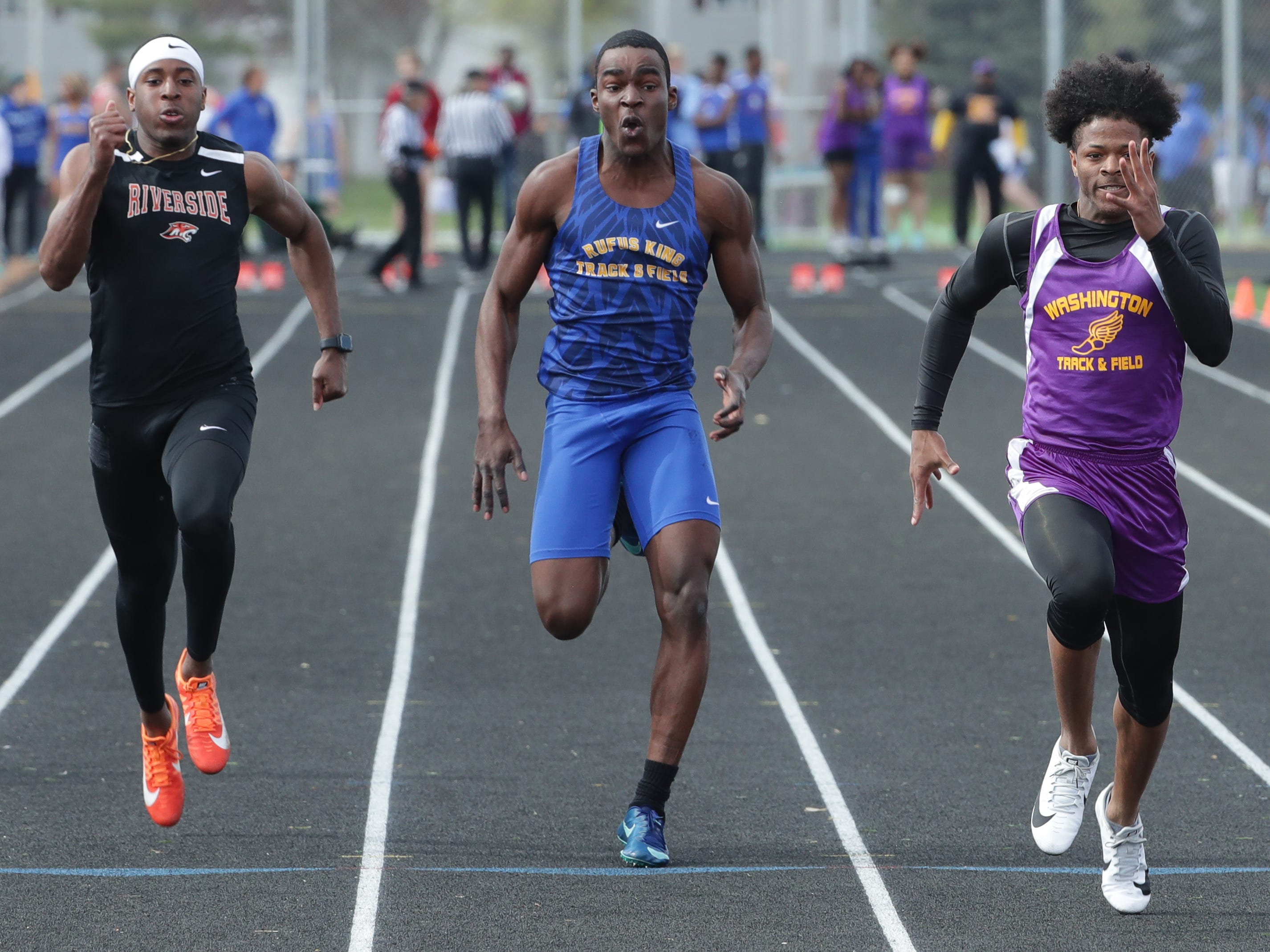 Washington's Elijah Johnson (front) wins the boys 100 meters with a time of 10.97 seconds at the City Conference track meet.