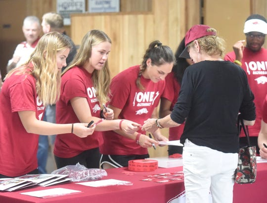 Members of the Arkansas Razorbacks women's tennis team hand out prizes at the ONE Razorback Roadshow on Tuesday night.