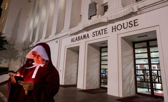 Anti abortion ban bill protestor Bianca Cameron-Schwiesow, dressed as a handmaid, waits outside of the Alabama statehouse after HB314, the near-total ban on abortion bill, passed the state senate in Montgomery, Ala., on Tuesday May 14, 2019.