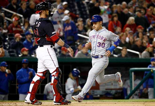 New York Mets' Michael Conforto, right, jogs past Washington Nationals catcher Yan Gomes for a run on a double by Brandon Nimmo during the sixth inning of a game Tuesday, May 14, 2019, in Washington.