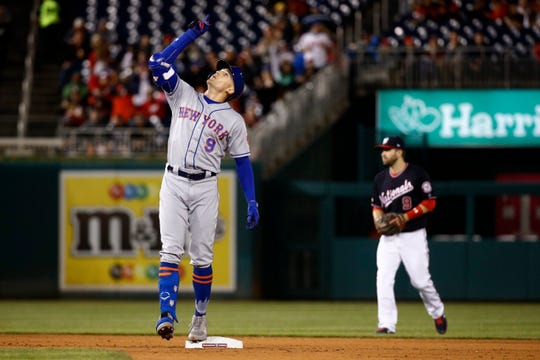 New York Mets' Brandon Nimmo, left, gestures near Washington Nationals second baseman Brian Dozier (9) after hitting an RBI double during the sixth inning of a baseball game Tuesday, May 14, 2019, in Washington.