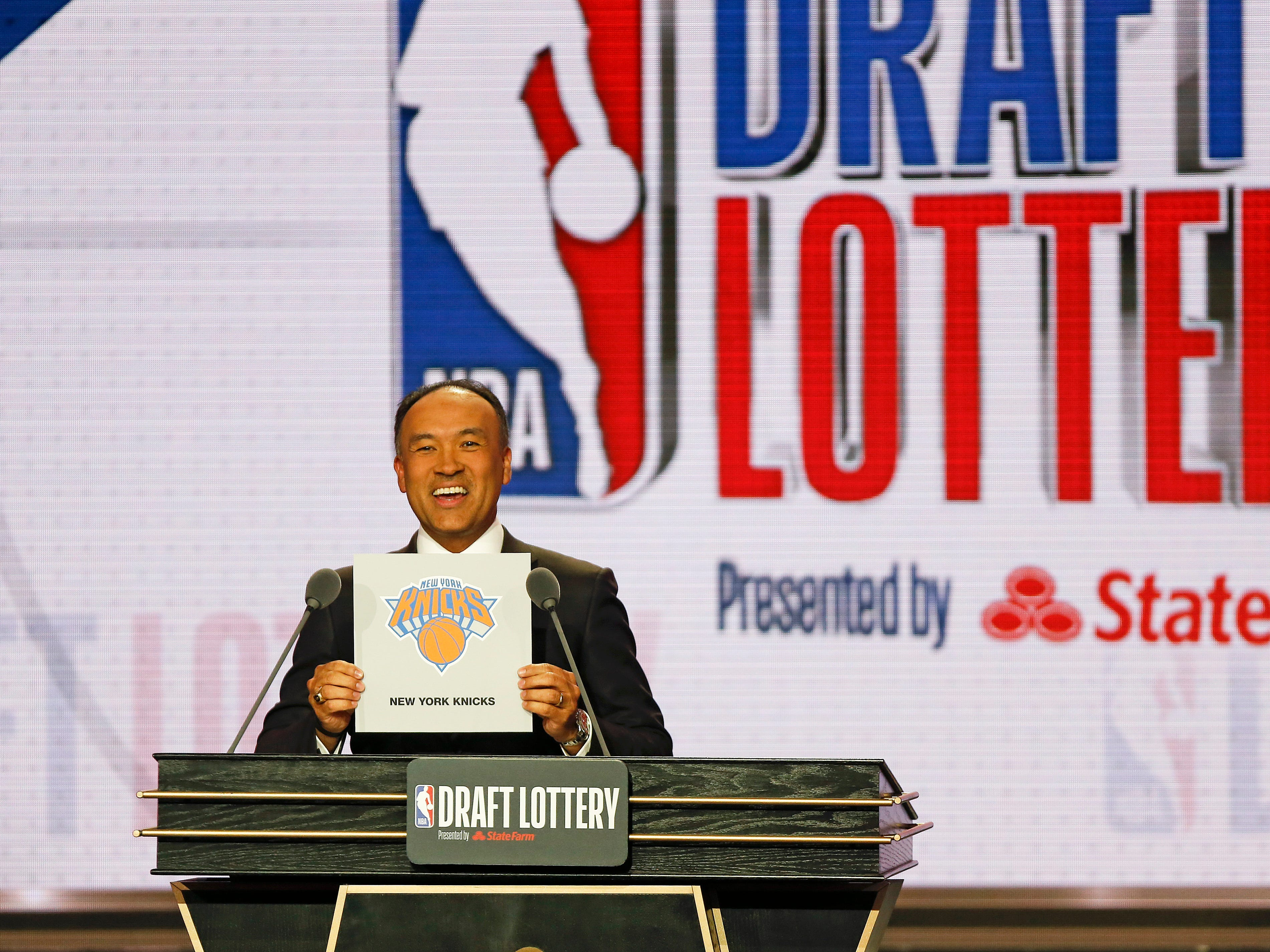 NBA Deputy Commissioner Mark Tatum announces that the New York Knicks had won the third pick during the NBA basketball draft lottery Tuesday, May 14, 2019, in Chicago. (AP Photo/Nuccio DiNuzzo)