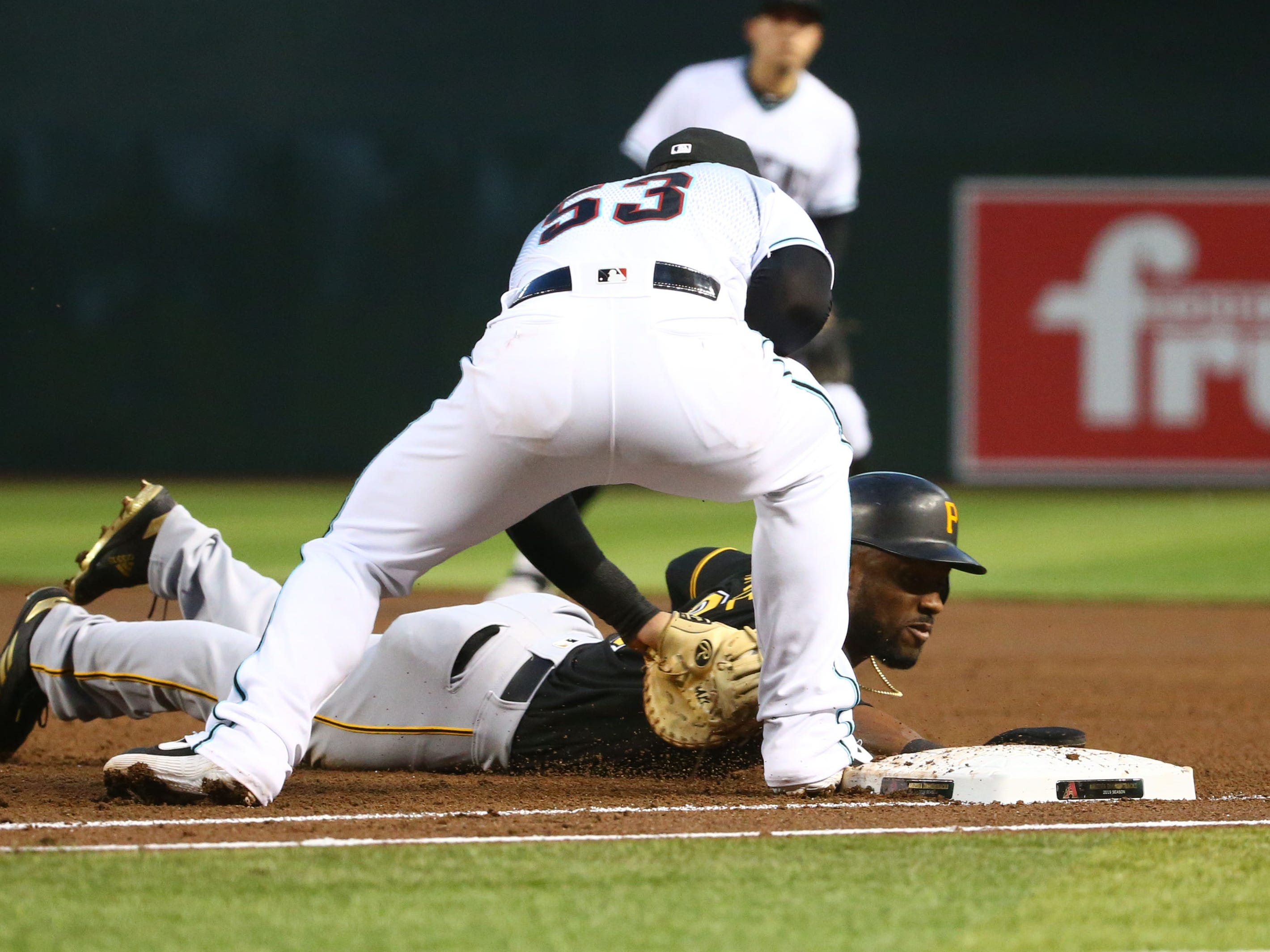 Pittsburgh Pirates Starling Marte dives safely back to first base past the tag by Arizona Diamondbacks 	Christian Walker in the third inning on May. 14, 2019 at Chase Field in Phoenix, Ariz.
