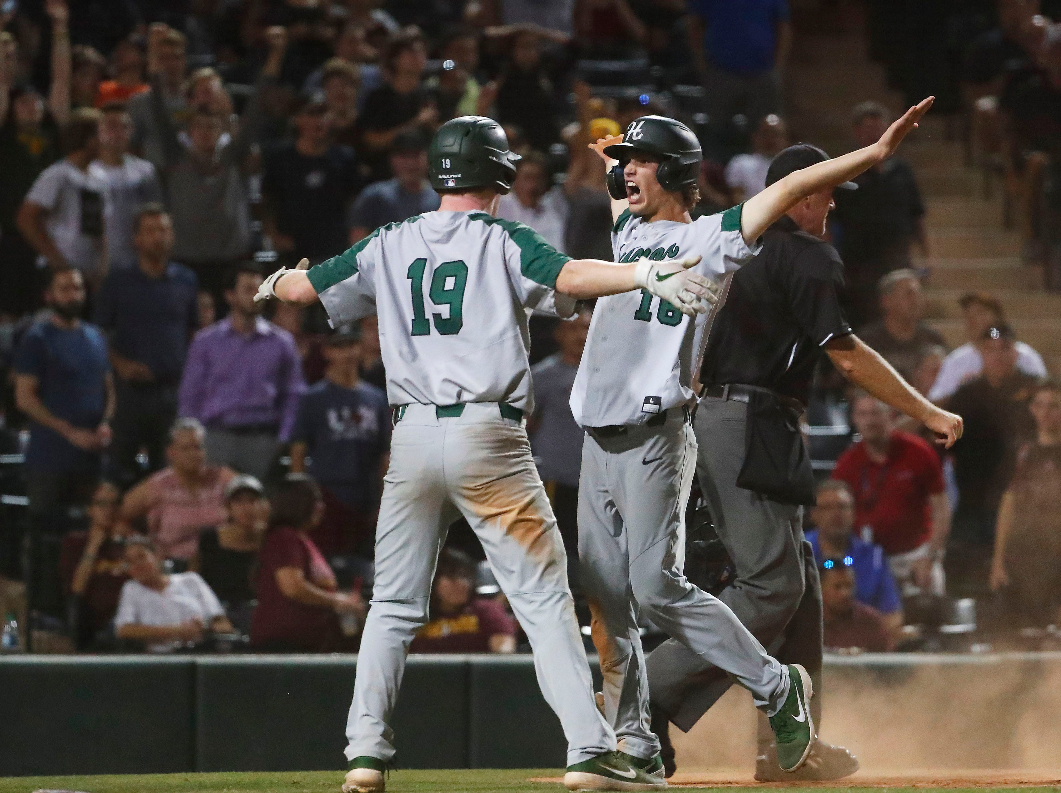Horizon's Brady Miltenberger (16) celebrates with Justin Lieberman (19) after scoring against Nogales in the 15th inning during the 5A State Baseball Championship in Tempe, Ariz. May 14, 2019.