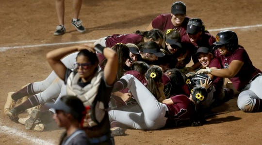 Salpointe players dog pile on the infield as Glendale Cactus players walk off after the Lancers scored the winning run in the eighth inning on Tuesday in Tucson.