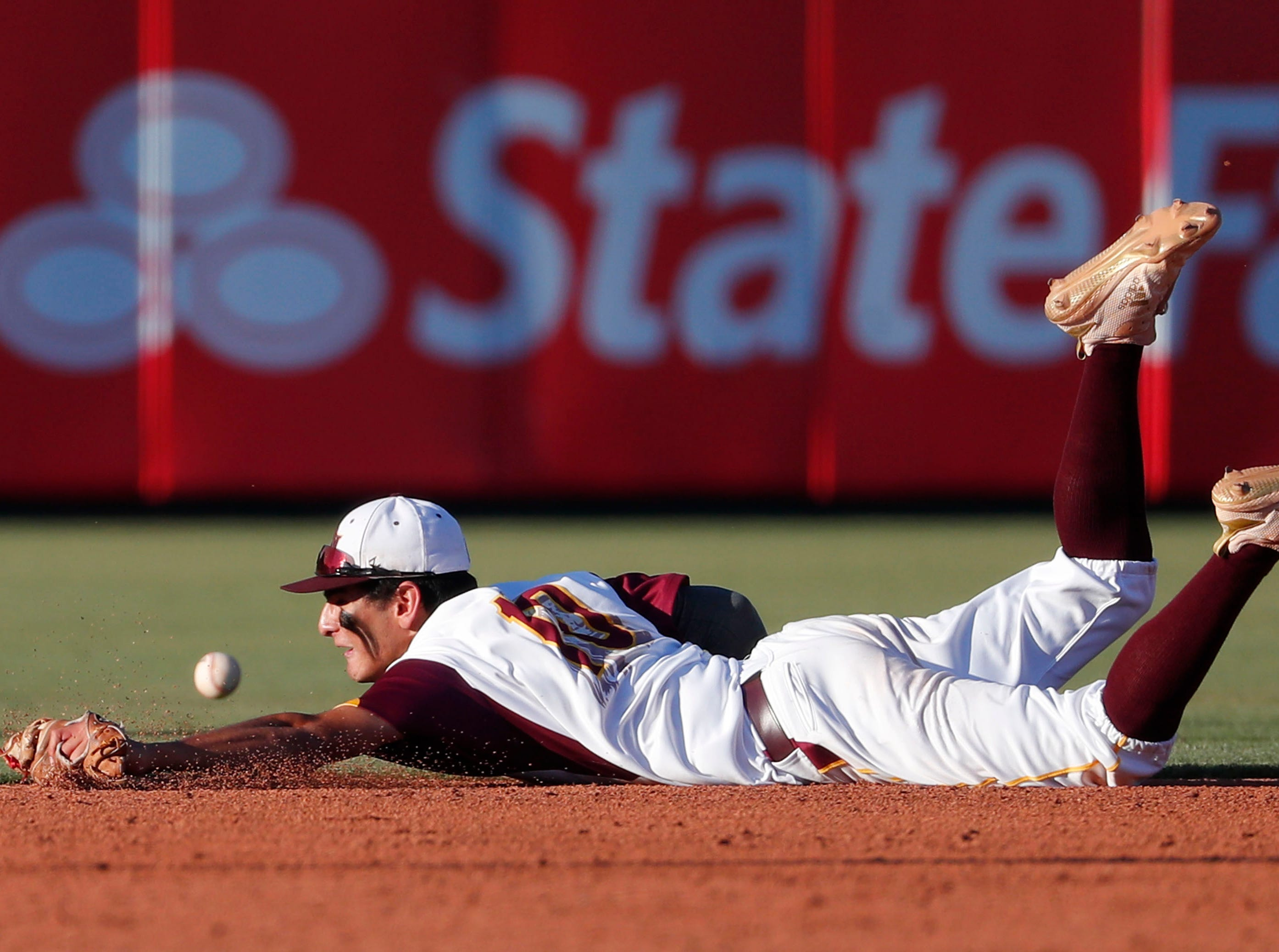 Nogales shortstop Jorge Bojorquez (10) dives for a base hit by Horizon during the 5A State Baseball Championship in Tempe, Ariz. May 14, 2019.
