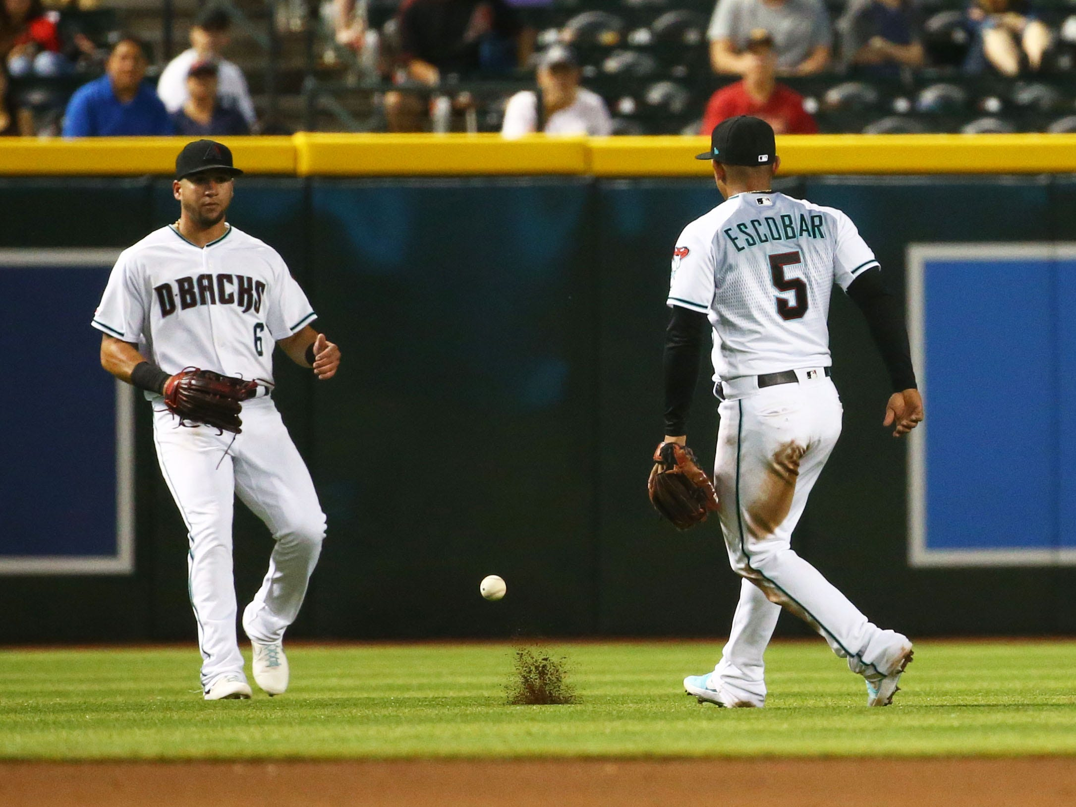 Arizona Diamondbacks David Peralta and Eduardo Escobar (5) watch the fly ball fall into left field hit by Pittsburgh Pirates Melky Cabrera in the fifth inning on May. 14, 2019 at Chase Field in Phoenix, Ariz.