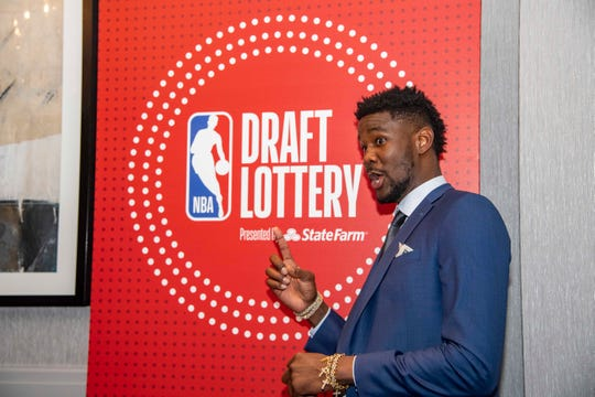 Suns center Deandre Ayton points to the NBA draft lottery logo on May 14 at the Hilton Chicago.