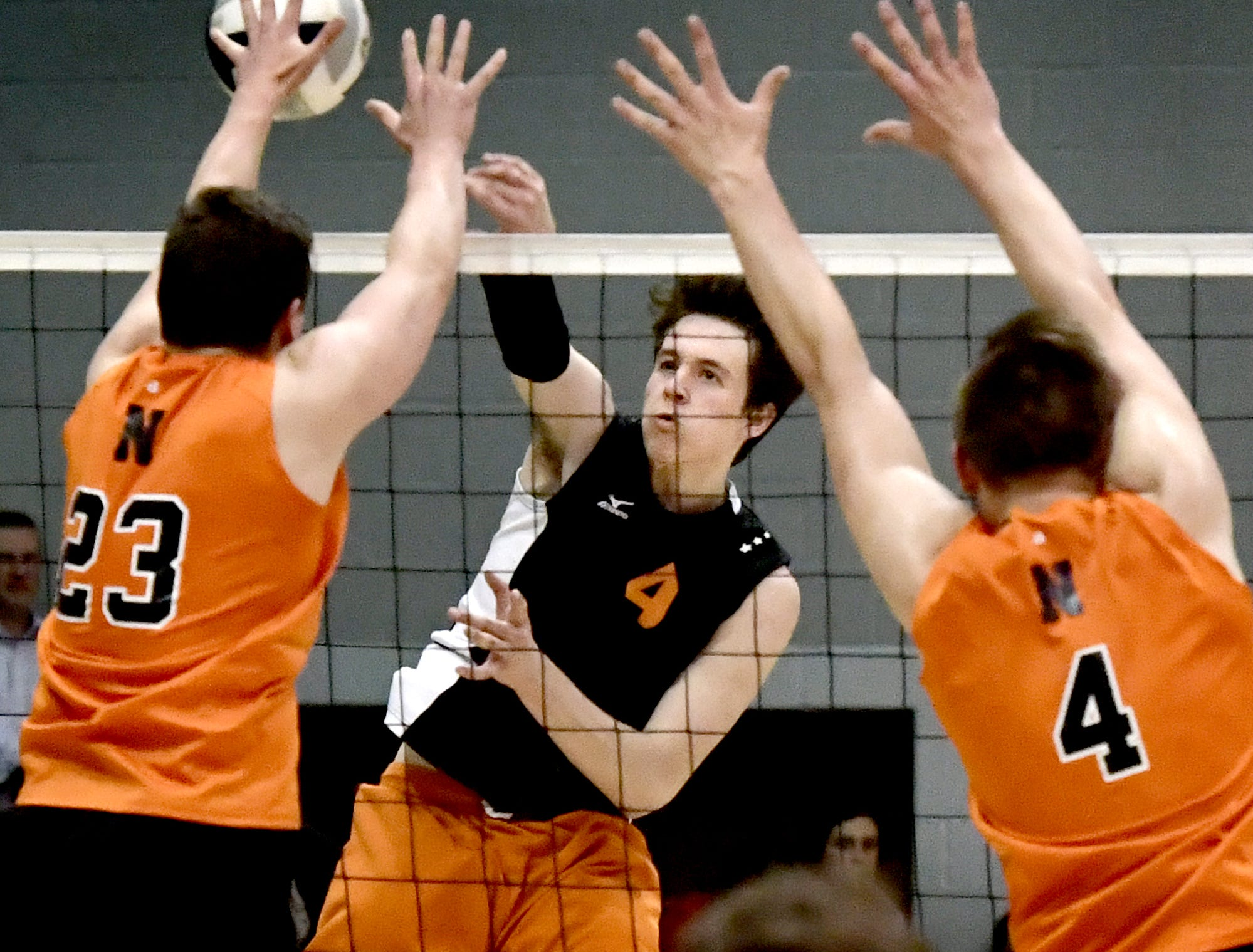 Central York's Matt Minkin fires a shot at Northeastern's Kyle Williams, left, and Zech Sanderson in the York-Adams boys' volleyball championship match at Dallastown Tuesday, May 14, 2019. Bill Kalina photo