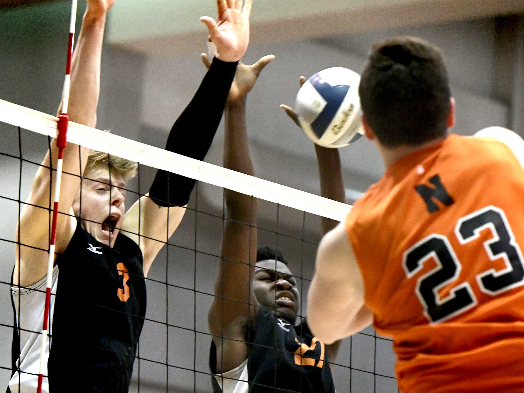 Central York's Kyle Mehl, left, and Prince Gabriel attempt to block a shot by Northeastern's Kyle Williams in the York-Adams boys' volleyball championship match at Dallastown Tuesday, May 14, 2019. Bill Kalina photo