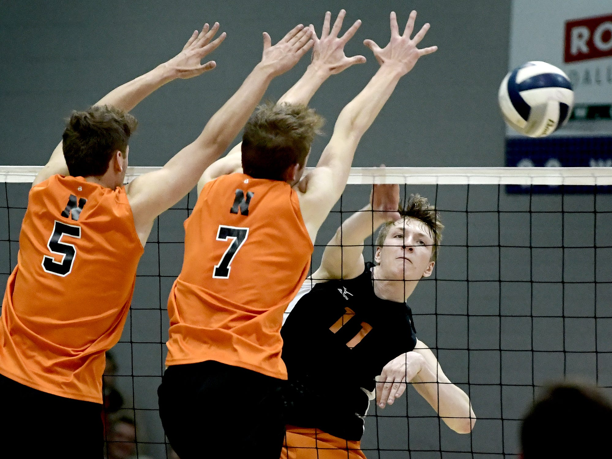 Central York's Braden Richard beyond the reach of Northeastern's Nate Wilson, left, and Alex Finch in the York-Adams boys' volleyball championship match at Dallastown Tuesday, May 14, 2019. Bill Kalina photo