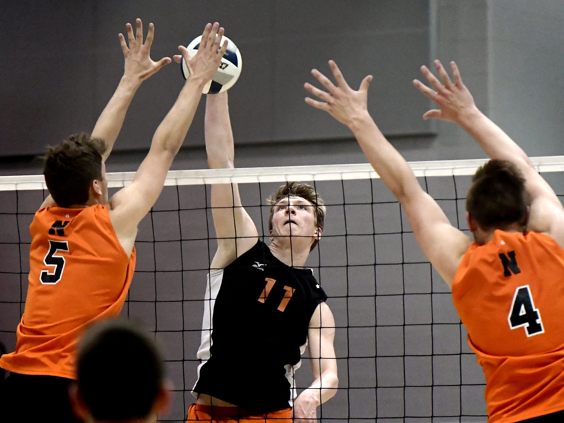 Central York's Braden Richard tips a shot over Northeastern's Nate Wilson, left, and Zech Sanderson in the York-Adams boys' volleyball championship match at Dallastown Tuesday, May 14, 2019. Bill Kalina photo