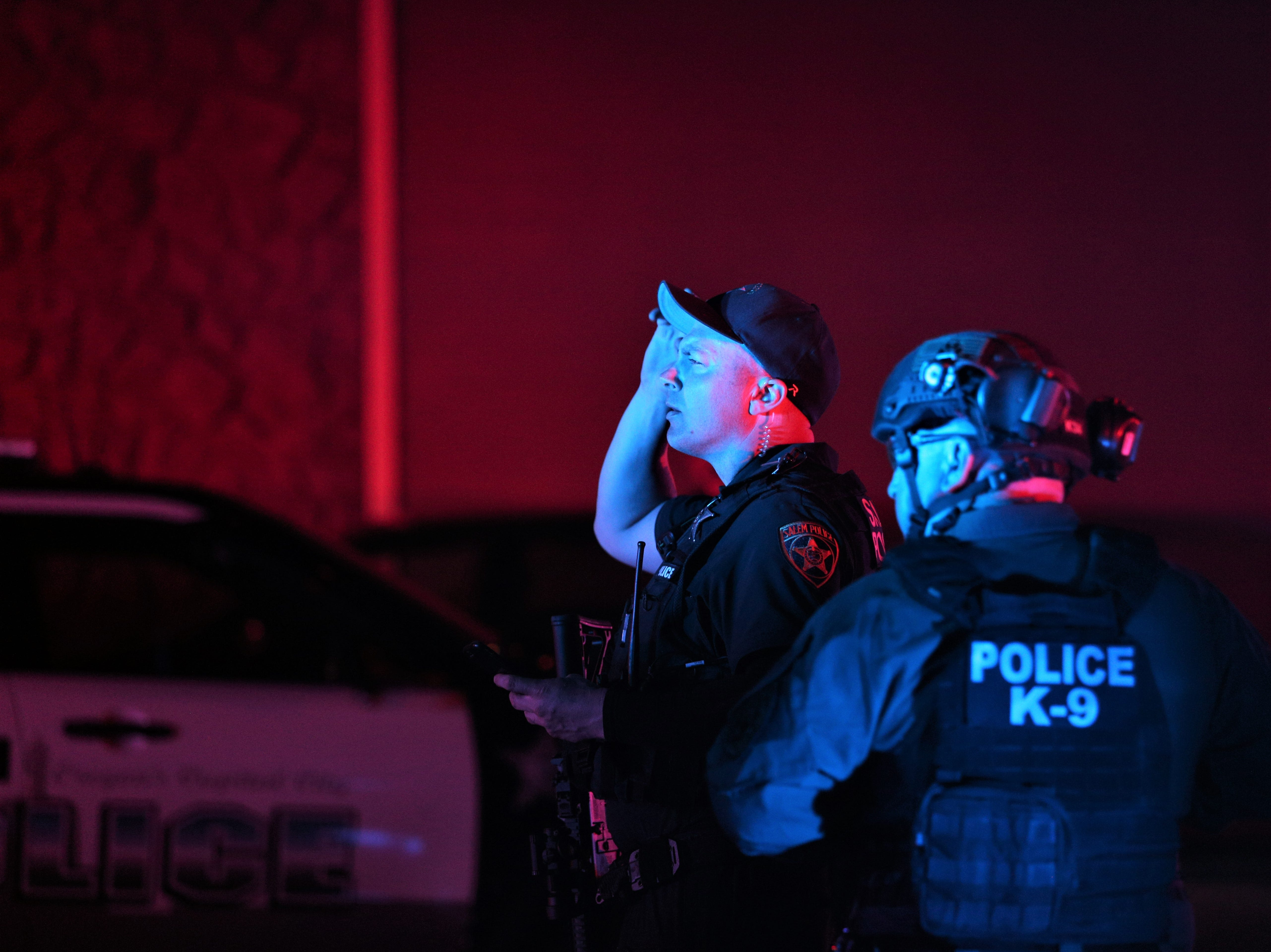 Law enforcement officers conduct a manhunt for a suspect who shot and injured a Salem Police officer near Highland Elementary School on May 14, 2019.