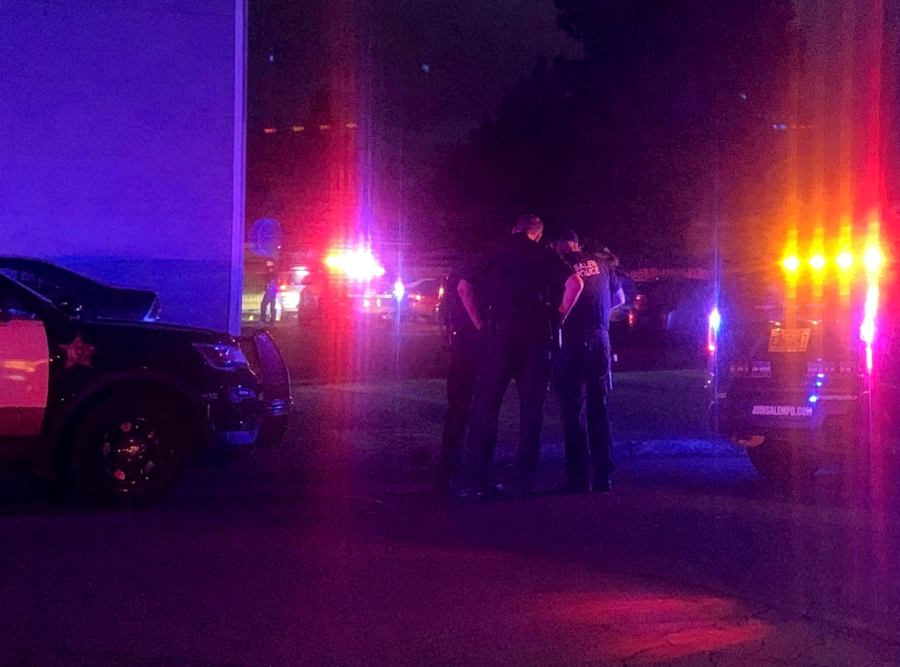 Salem police officers surround an apartment complex at the intersection of Locust and Broadway in Salem.