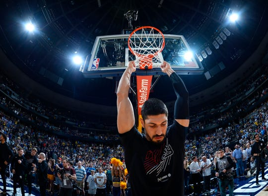 Portland Trail Blazers center Enes Kanter hangs on the net before the first half of Game 7 of an NBA basketball second-round playoff series against the Denver Nuggets May 12, 2019, in Denver.