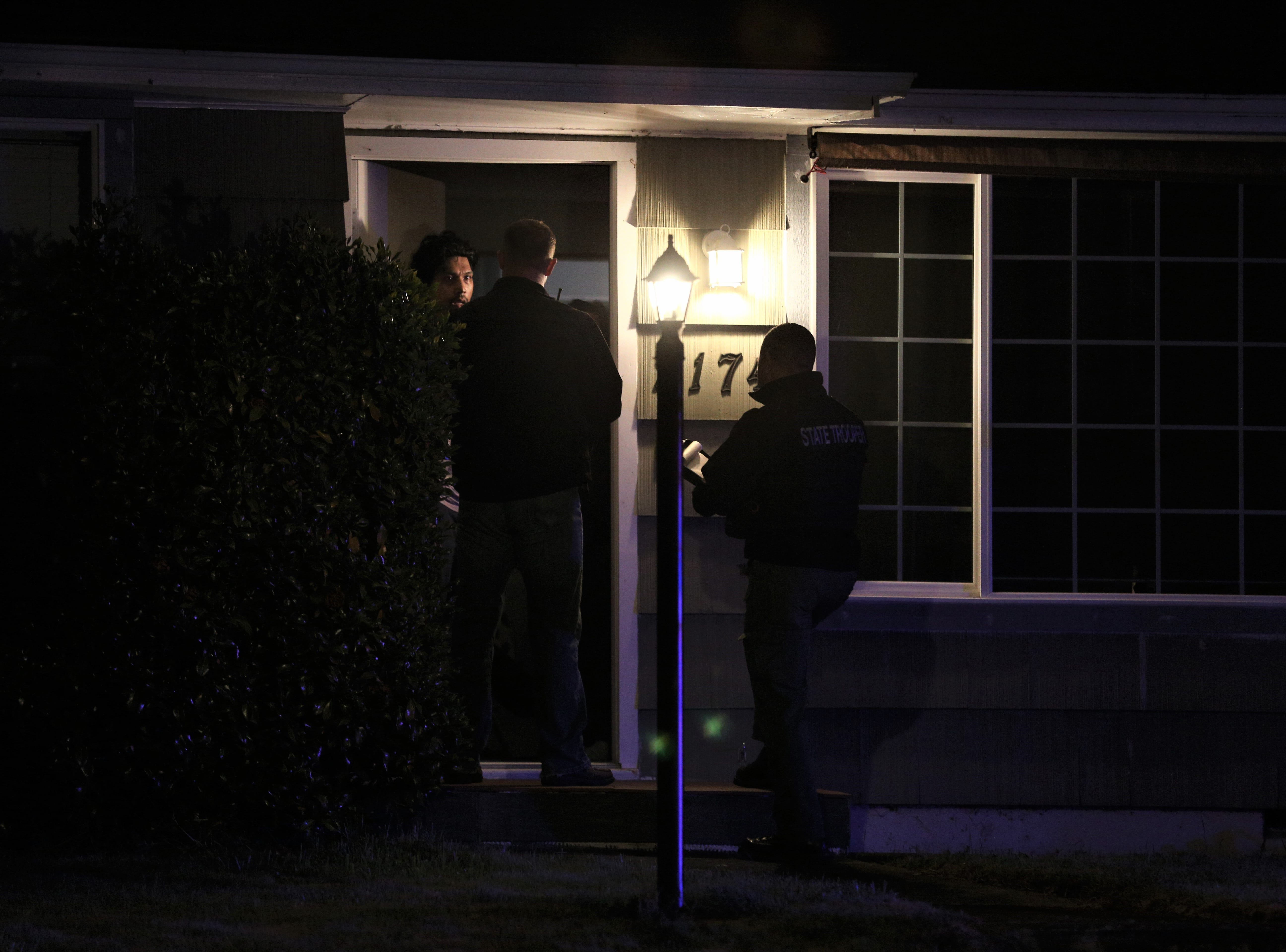 Law enforcement officials knock on doors near Highland Elementary School where a Salem Police officer was shot in Salem on May 14, 2019.