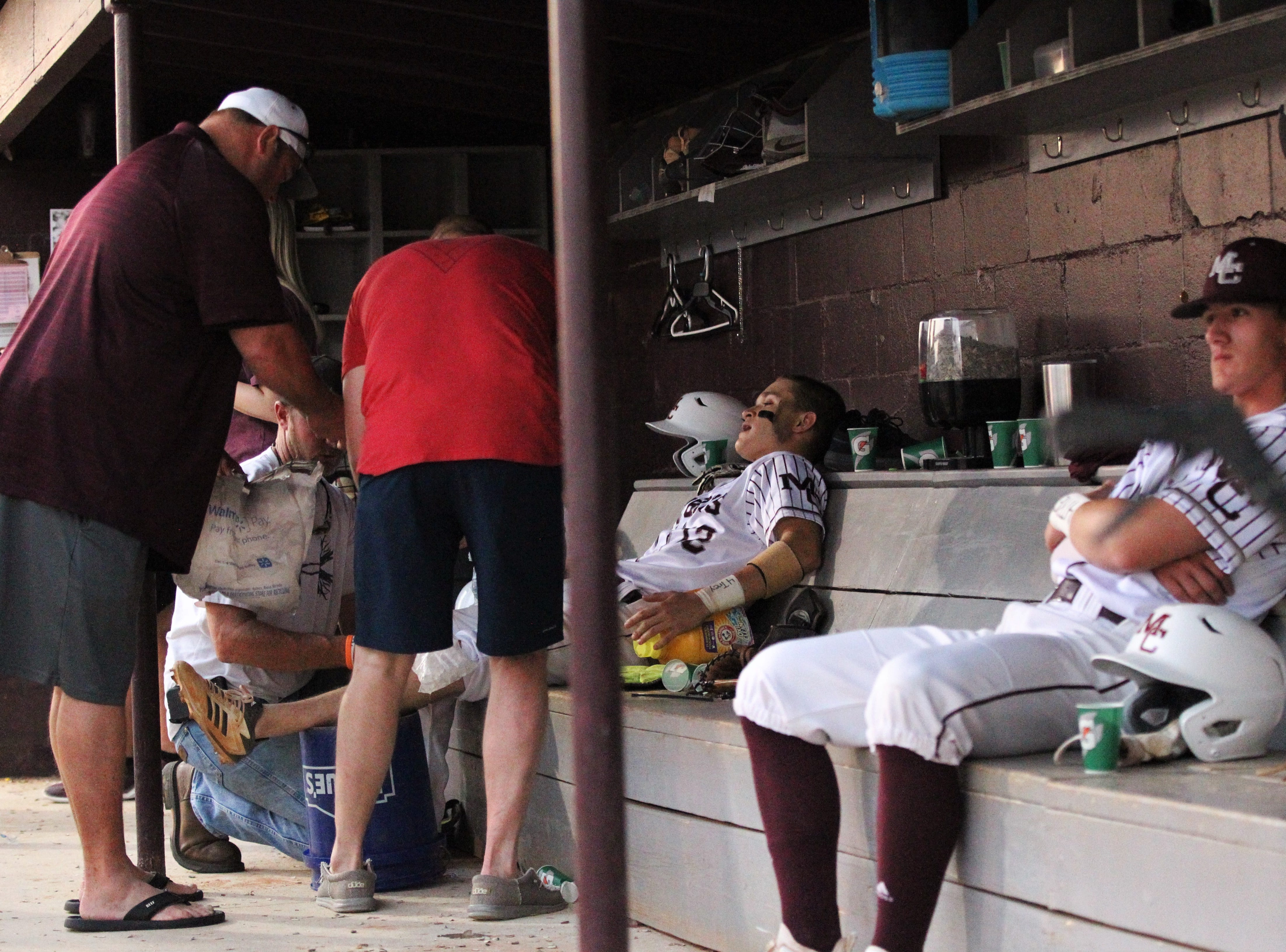 Madison County catcher Logan Lepper gets treatment on an injured knee as the Cowboys beat Union County 1-0 during a Region 2-1A semifinal on May 14, 2019.