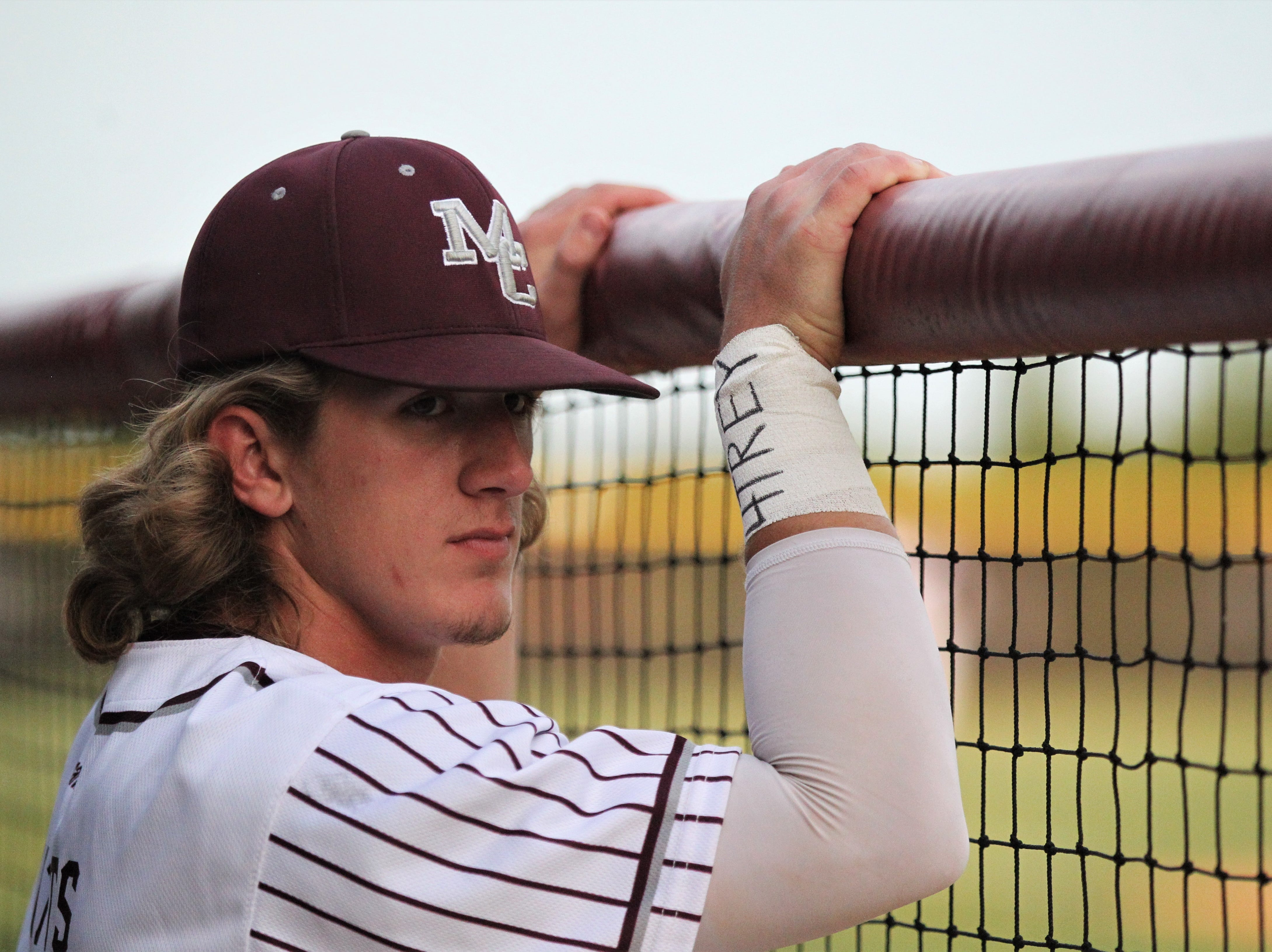 """Madison County senior Caleb Watts, wearing tape that says """"4 Trey"""", watches as the Cowboys beat Union County 1-0 during a Region 2-1A semifinal on May 14, 2019 and played for former player Trey Mitchell, who died last week during a drowning accident."""