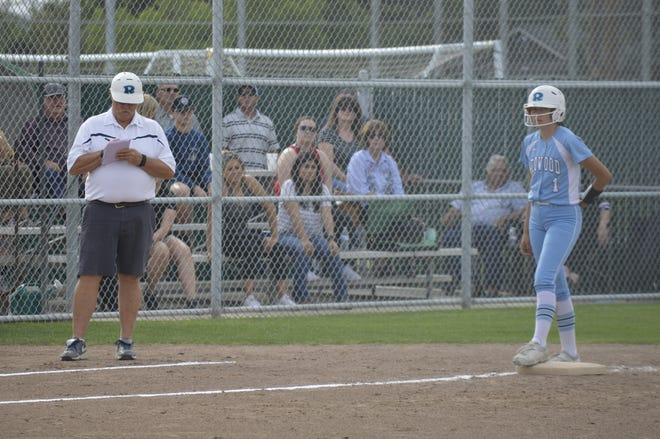Redwood High school softball head coach Bob Rooney, left, takes notes as Mariah Guerrero reaches third base on May 14, 2019. Guerrero is Rooney's granddaughter.