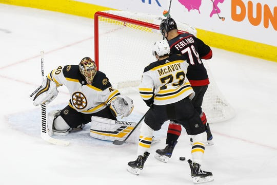 Bruins goaltender Tuukka Rask makes a save on Hurricanes left wing Micheal Ferland as Bruins defenseman Charlie McAvoy defends in the first period of Game 3.