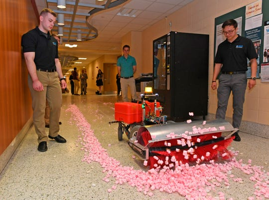 Gannon University engineering students Niklas Bitters, Mitch Wesley and Tenger Batjargal watch as their autonomous snow-removal robot moves along a hallway at the Zurn Science Center in Erie, Pa., on Friday.