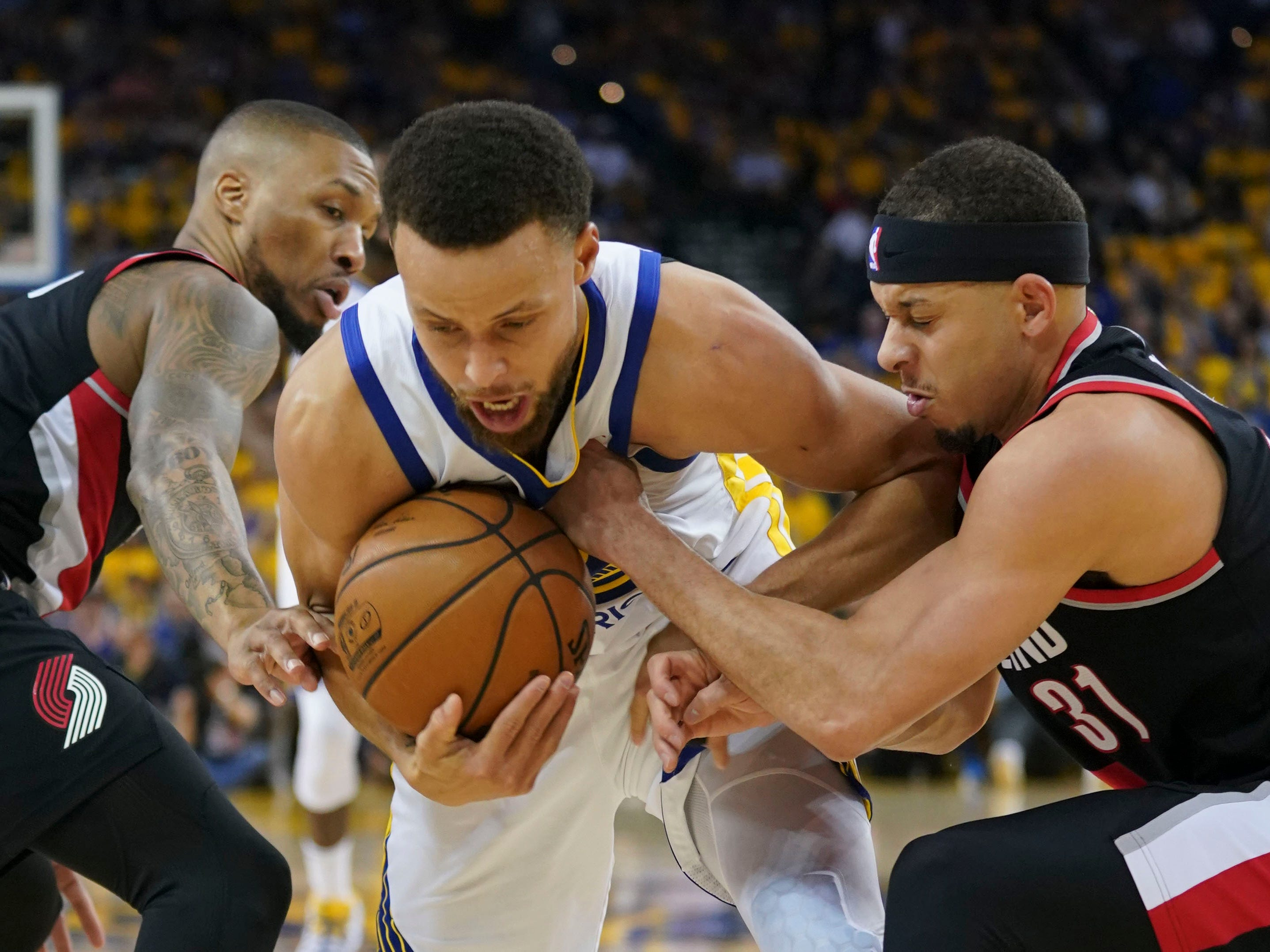 May 14: The Golden State Warriors' Stephen Curry is defended by the Portland Trail Blazers' Damian Lillard (0) and Seth Curry (31) during the second quarter in Game 1 of the Western Conference finals at Oracle Arena. The Warriors won the game, 116-94.