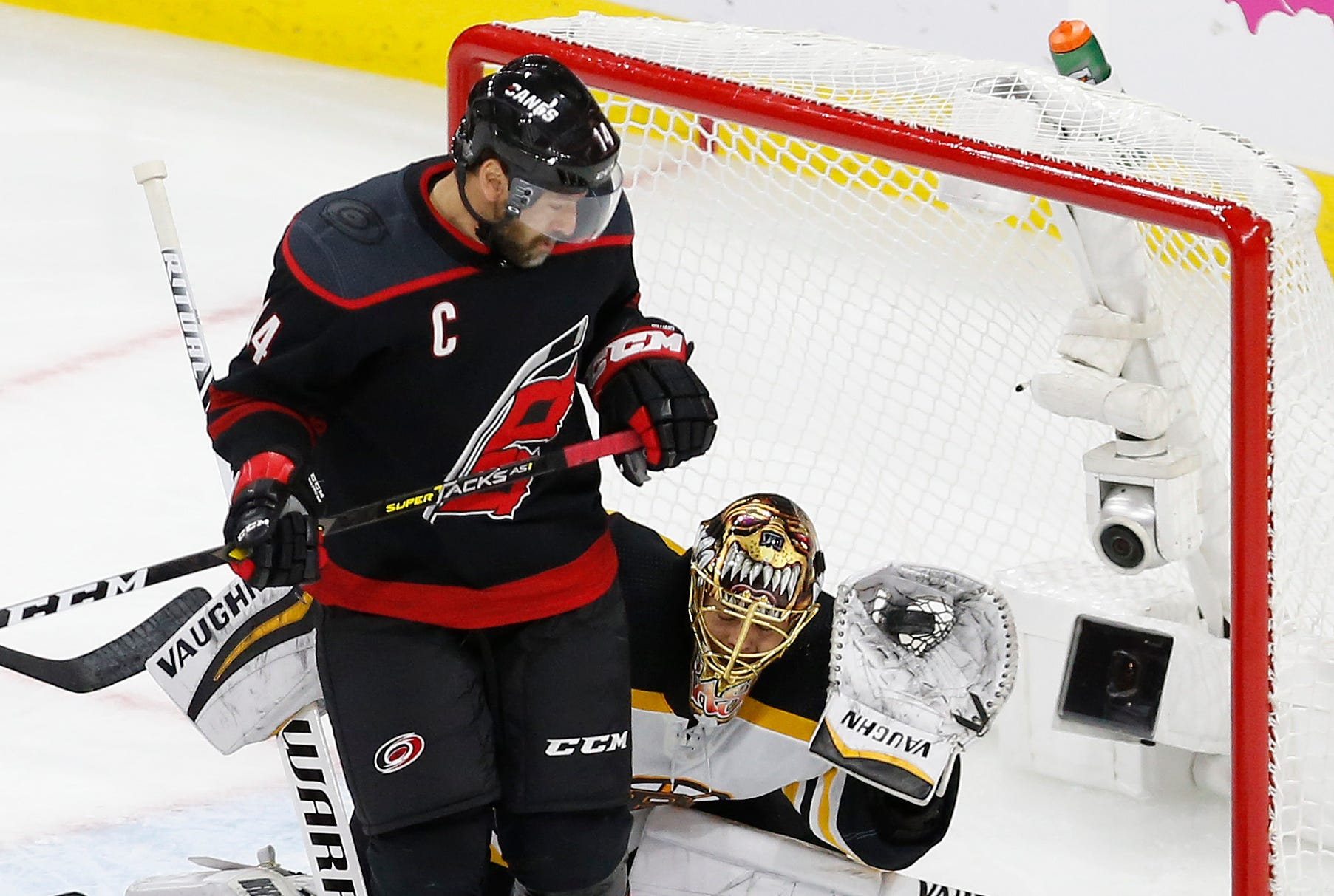 Conference final: Bruins goaltender Tuukka Rask looks around a screen set by Hurricanes captain Justin Williams to make a glove save in Game 3.
