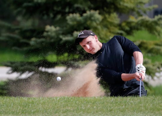 Kaukauna's Brock Hlinak hits out of a bunker during the Fox Valley Association conference meet May 17, 2019, at Chaska Golf Course in Greenville.