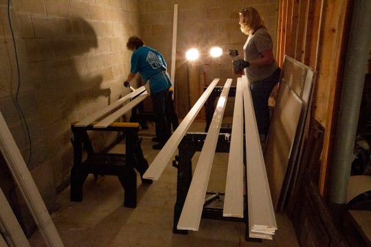 Freeholder Sue Kiley and volunteer Kim Stulb of Hazlet work on painting trim in the basement of a Keansburg house under construction by Habitat for Humanity in Monmouth County.