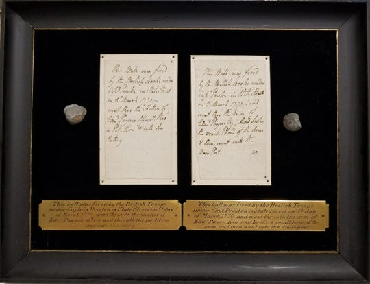 The framed board on which the musket balls were mounted, along with two undated handwritten notes explaining their histories.