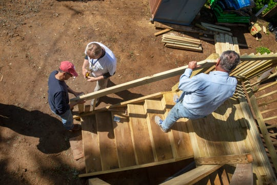 Workers put a railing on front steps to the house as another day gets started at the Keansburg home under construction by Habitat for Humanity in Monmouth County.
