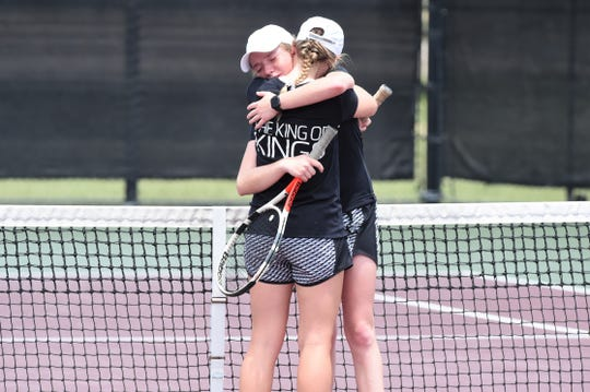 Rising Star's Caryn Lawrence and Abby Geye hug following the Class 1A girls doubles final.
